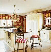 Two upholstered metal bar stools at a kitchen bar in an elegant, country house-stlye fitted kitchen with a chandelier