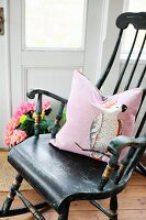 Nostalgic wooden rocking chairs with pink scatter cushion in Nordic country-house interior