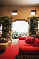 Contemporary living room with red furniture and view of plants through arched opening; Scottsdale; USA