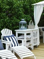 White-painted sun loungers with scatter cushions next to lantern on side table with castors on wooden deck