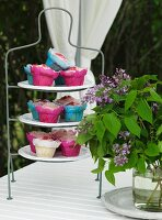 Muffins in colourful paper cases on cake stand and vase of lilac on garden table