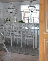 Dining room with white wooden chairs around table below chandeliers with glass ornaments