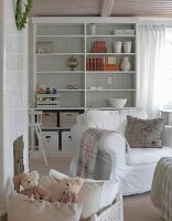 White armchair in front of shelving with box of cushions and soft toys in foreground