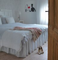 Dress on double bed with white bedspread in bedroom