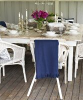 Lit candles on festively set table and white wicker chairs on wooden floor