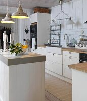 Bowl of fruit and candles on counter below retro pendant lamp in white, country-house-style kitchen