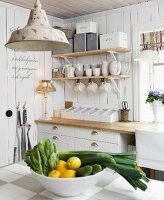 View across kitchen counter with bowl of lemons and vegetables to white crockery on wall-mounted shelves