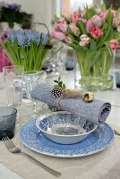 Table set with blue and white crockery, napkin decorated with quail eggs and vases of spring hyacinths and tulips