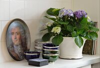 Potted hydrangea, Moroccan dishes with silver rims and historical portrait on try on surface