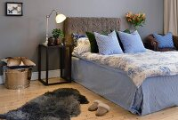 Bed with upholstered headboard and blue and white bed linen against grey-painted wall