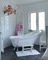 Free-standing vintage bathtub in white bathroom with charcoal grey floor tiles