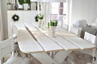 White shabby-chic interior in Scandinavian wooden house with rustic dining table and printed lettering on chair cushions