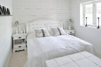 Romantically decorated double bed and bedside tables in pure white, shabby-chic bedroom in Scandinavian wooden house