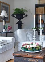 Wreath of flowers in front of lit candles in white, ceramic candlesticks on wooden trunk in corner of living room
