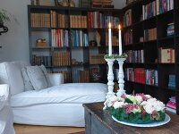 Wreath of flowers and lit candle in white candlesticks on trunk; white couch and L-shaped bookcase in background