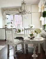 White-painted, Biedermeier-style side table in front of dining area below chandelier with glass pendants in country-house kitchen