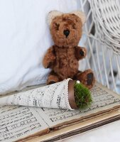Pot of moss in sheet music cone next to teddy bear