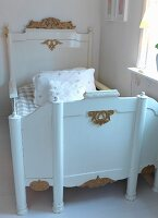 Antique child's bed painted white with gilt embellishments in corner of nursery