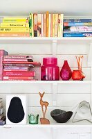 Books arranged by colour, vases and stylised deer ornament on white shelves