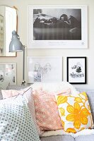 Gallery of pictures and desk lamp above corner sofa with retro scatter cushions