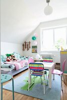 Play table and colourful chairs on rug with animal motif in front of bed with patchwork counterpane in child's bedroom