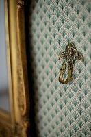 Brass hook on wall with ornately patterned wallpaper