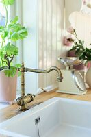 Kitchen sink with vintage brass tap below window