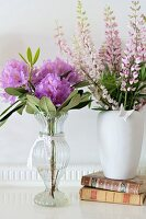 Vases of flowers and books on white surface