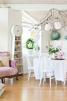 White dining set next to rustic long-case clock with integrated shelves next to Baroque-style sofa