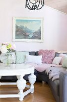 White coffee table in front of grey corner couch with scatter cushions below landscape painting on pastel pink wall