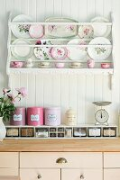 Decorative plates on white plate rack above pale kitchen base units