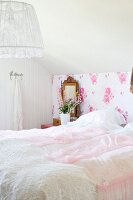 Double bed with pink lace bedspread against vintage-style floral wallpaper