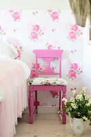Pink-painted chairs with carved backrest and seat cushions against floral wallpaper next to pot of flowers on floor