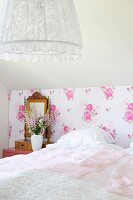 Bedroom with white bedspread on bed, nostalgic floral wallpaper and pendant lamp with lace lampshade