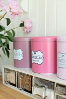 Retro storage tins in shades of pink on spice rack