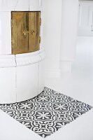 Patch of tiles with Oriental pattern in front of traditional tiles stove with brass door in white, purist interior