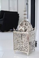 Silver, Oriental-style lantern on white floor