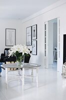 Vase of white lilies on tray table in black and white living room