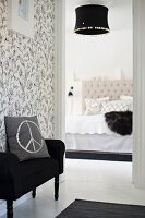 Cushion with CND symbol on black couch against floral, black and white wallpaper outside elegant bedroom with black lampshade