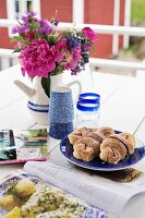 Bouquet in jug, beakers, plate of pastries and magazines on garden table