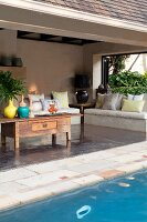 Pool in front of roofed terrace with rustic coffee table; concrete bench with cushions in background