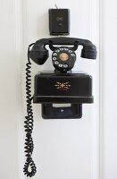 Black vintage telephone mounted on white wooden wall