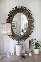 Oval mirror with sunburst metal frame behind Bourgie Lamp by Ferruccio Laviani on surface