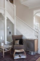 Armchair and magazine rack next to 50s-style speaker at foot of staircase with white-painted, wooden balustrade in foyer