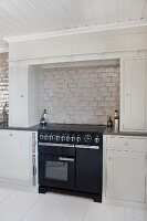 Black cooker in niche between pale grey fitted cupboards with pale grey tiles