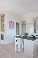 Pale grey island counter and bar stool in open-plan, country-house kitchen
