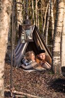Woman and man lying in makeshift tent looking at autumn woods; vintage ambiance