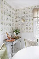 Delicate console table against wall with white wainscoting and botanical wallpaper