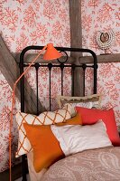 Orange retro standard lamp next to black metal bed with collection of scatter cushions in shades of orange and wallpaper with pattern of coral