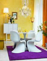 Gold wallpaper, Panton chairs and purple rug